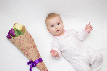 Very beautiful, cute baby lies on a white plaid next to a bouquet of tulips and Smiles