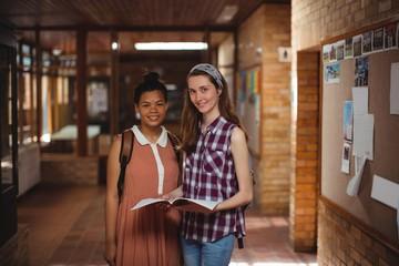 School kids holding books in corridor at school