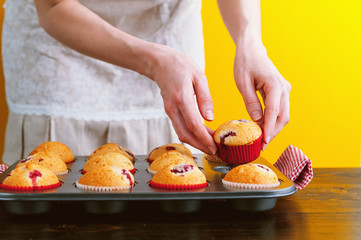 Chef with muffins on a bright yellow background