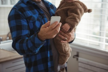 Father using mobile phone while holding his baby in kitchen