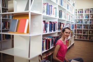 Portrait of smiling schoolgirl in library