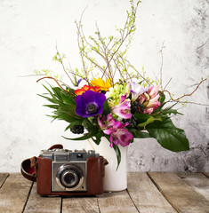 Old Vintage Camera with Beautiful Bouquet of Flowers on Wooden Background. Old Vintage Holiday Concept.