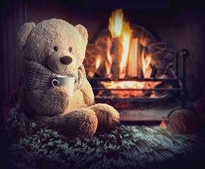 A teddy bear is sitting by the fireplace with a cup