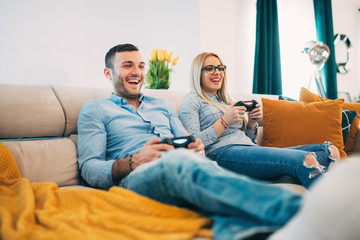 young couple having fun and laughing while playing video games in modern living room
