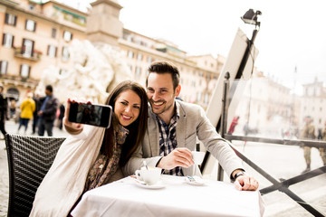 Young couple taking selfie in the restaurant in Rome, Italy