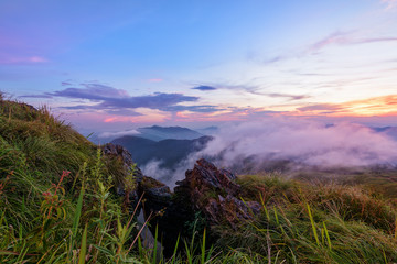 Beautiful landscape nature on peak mountain with sun cloud fog and bright colors of sky and sunlight during sunset in winter at viewpoint Phu Chi Fa Forest Park in Chiang Rai Province, Thailand