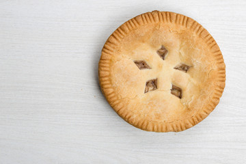Apple pie cake lying on wooden white background