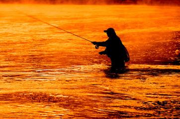 Silhouette of Man Flyfishing in River