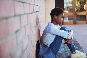 Sad schoolgirl sitting against brick wall Wall mural