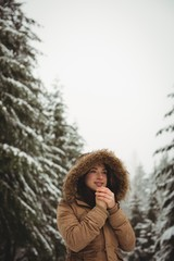 Beautiful woman in warm clothing warming her hands