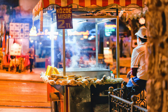 Male street fast food seller with pan corn on traditional turkish cart. Istanbul, Turkey. Night scene.