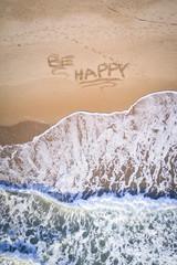 Be Happy written on the beach