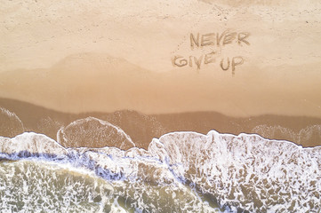 Never give up written on the beach