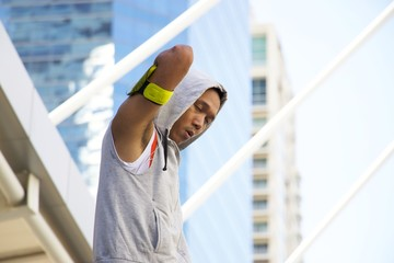 Sporty man is exercising in the city. He is stretching his body and warming up himself before goes jogging.