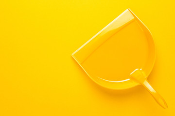 top view of plastic dustpan on yellow background