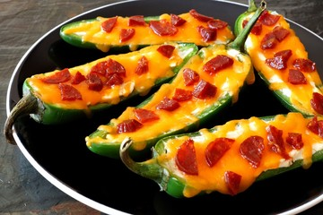 Group of jalapeno poppers with cheese and pepperoni close up on a black plate
