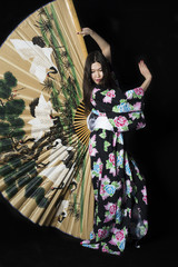 Japanese girl in traditional Japanese kimono with a large fan on a black background.