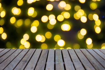 Empty wooden table or plank with bokeh of light from xmas tree on background for product display.
