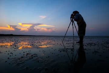 Silhouette of photographer man in sunset.