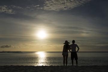 夕暮れのビーチと男女のシルエット