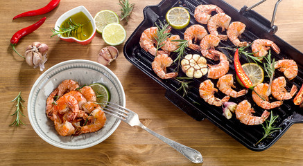 Shrimps roasted with lemon slices and garlic  on grill pan.