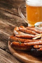 German food, Oktoberfest menu. Mug of cold light beer and wooden platter with various grilled sausages, close up view. Restaurant photo, free space