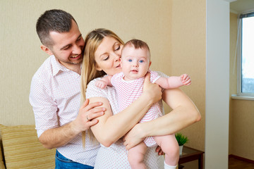 Mother and father with a baby in the room hugging smiling happy.Happy family.