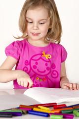 child draws wax pencils