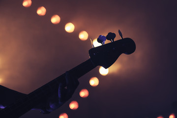 Bass guitar over bright blurred lights