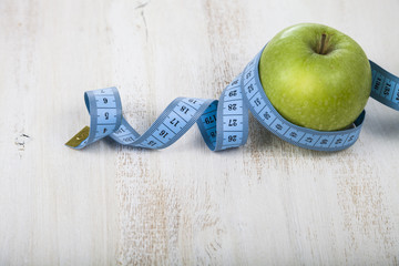 Green apple and measuring tape on a wooden table.