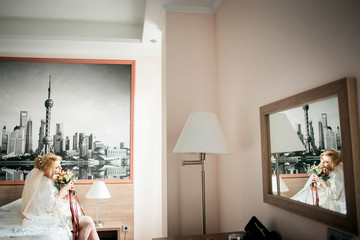 Gorgeous bride sits on bed in room with picture of modern city on the wall