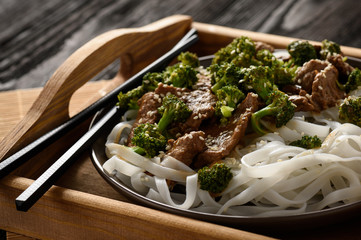 Chinese food - beef prepared with broccoli and rice noodles.
