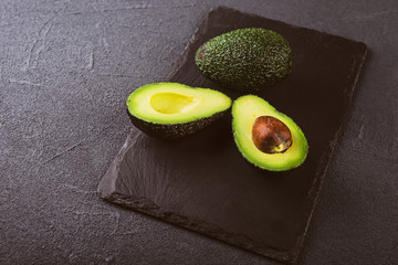 Fresh cutting avocado on stone board over wooden background