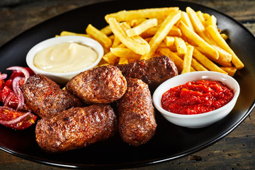 Deep fried cevapcici meat patties and potato chips