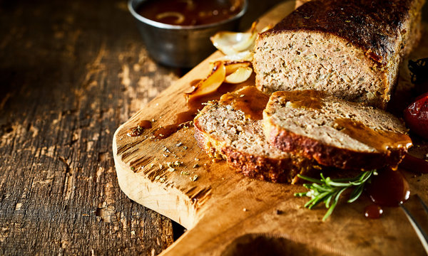 Sliced Meatloaf on Wood Board with Herbs and Gravy