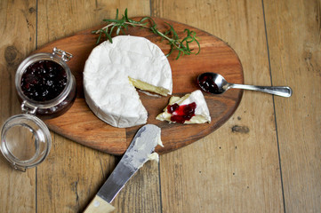 Delicious camembert cheese with cranberry on wooden background
