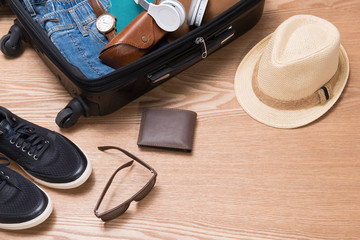 Travel and vacations concept. Open traveler's bag with clothing, accessories, credit card, tickets and passport.