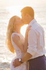 Young couple kissing on seaside at golden sunrise