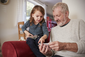Grandfather And Granddaughter At Home Looking At Photographs