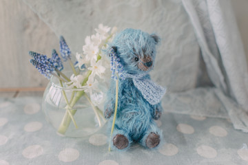 Blue teddy bear with a vase with flowers