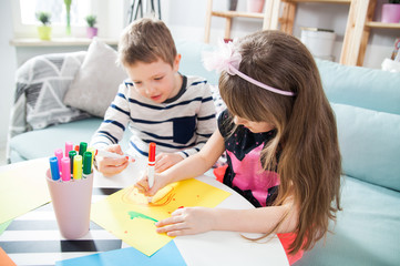 Brother and sister drawing with colorful pencils at home