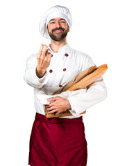 Young baker holding some bread doing coming gesture