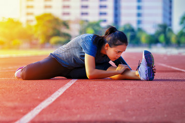 Young asian woman doing some warm up exercises before running