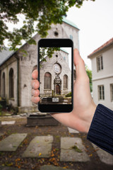 Hand with a smartphone close-up. On the smartphone display is a photograph of the church.