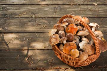 Forest Edible Mushrooms In Wicker Basket On Old Wooden Board Top View. Harvesting Mushrooms.