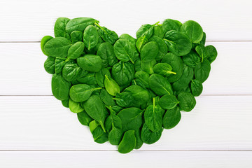 Heartshaped sign made of fresh green spinach leaves