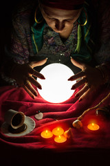 Female fortuneteller with her hands above crystal ball