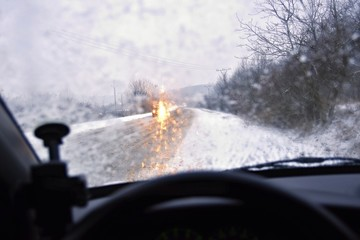 Driving in bad snowy weather and cars in the fog. Bad winter weather and dangerous automobile traffic on the road.Light vehicles in fog.