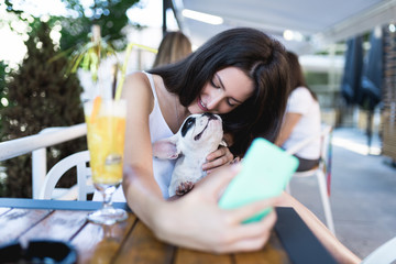 Beautiful young woman in a cafe taking selfie photo with her French bulldog puppy.