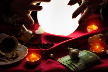 Hands of fortune teller around crystal ball